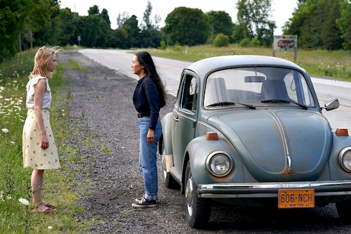 two women standing on road next to car