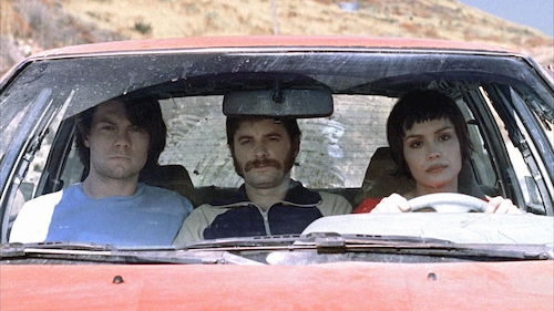 three people sitting in red car